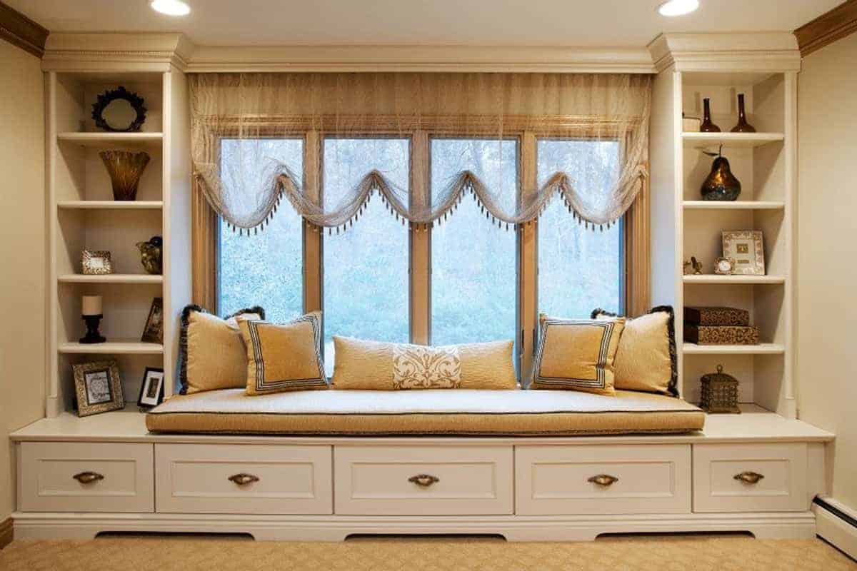 Custom-built window seat provides a cozy nook to read and great focal point in this master bedroom sitting area in Roslyn NY home interior design.
