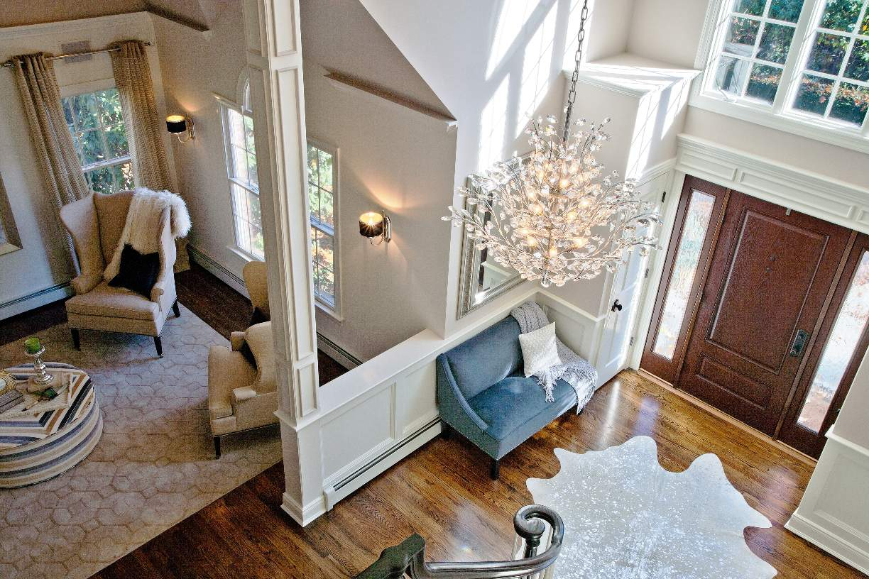 Elegant crystal chandelier floral design gives organic feel that balances well with earth tone wood floor, Northport NY interior design.