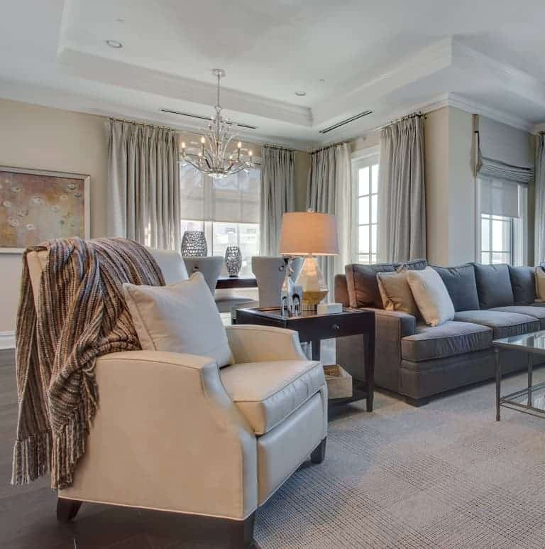Open concept family room in Ritz-Carlton Residences, North Hills, Manhasset NY designed by Robyn B of Interiors By Just Design. Duralee sectional sofa and chair, Kravet rug, Design Master chairs, Century dining room table, custom window treatments, Visual Comfort chandelier.